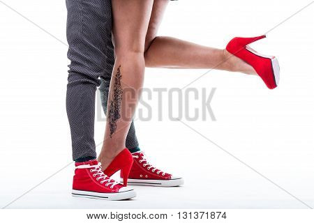 red sneakers of a man red high heels shoes on long legs of a sexy woman
