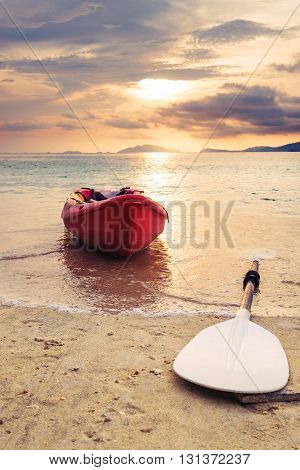 Kayak with oar on the beach in sunset