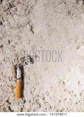 A cigarette in sand ashtray for background.