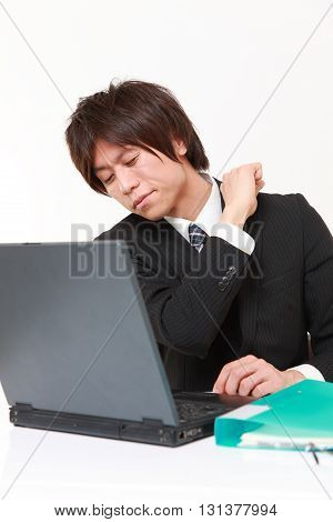studio shot of young Japanese businessman suffers from neck ache on white background