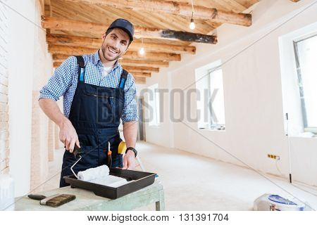 Smiling handsome young builder using paint roller while working indoors