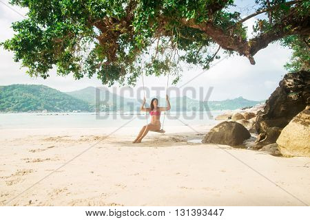 Young, beautiful lady swinging in the shade under an old tree on the beach in Thailand.