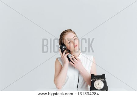 Relaxed woman with closed eyes speaking on retro phone isolated on a white background