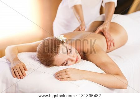 Beautiful young woman lying on massage table and therapist massaging her back