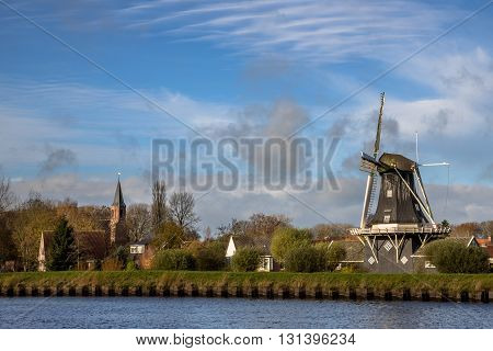 Windmill And Church In Small Village Of Woltersum
