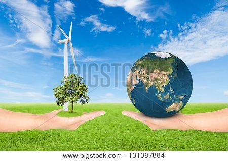 Green Earth concepthand holding tree with wind turbine and earth against green field and blue sky background.Elements of this image furnished by NASA