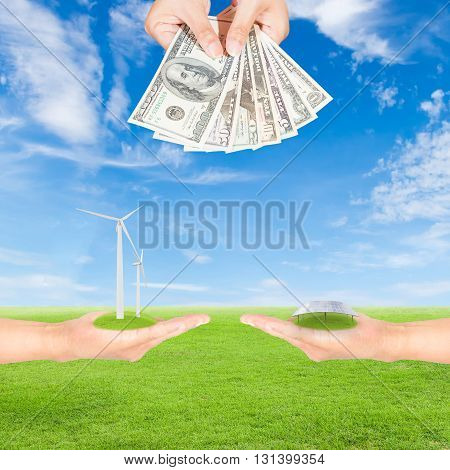 Carbon credits concepthand holding wind turbine solar panels and US Dollars banknote against green field and blue sky background