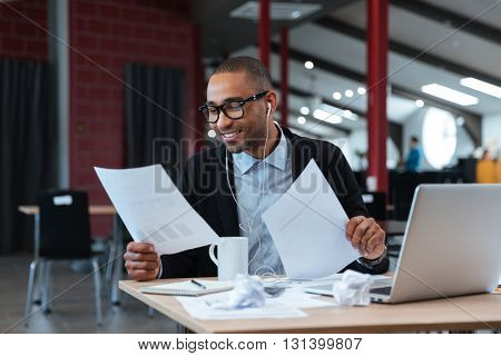 Handsome smiling businessman looking at documents and listens to music