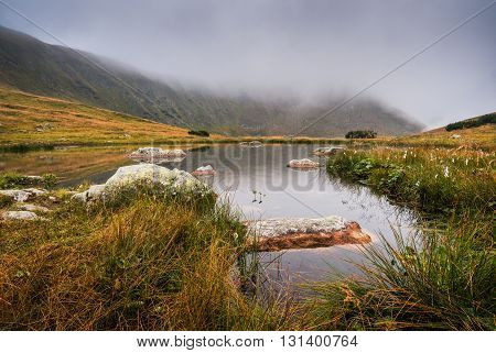 Small Tarn with Rocks in Foggy West Tatra Mountains in the Evening