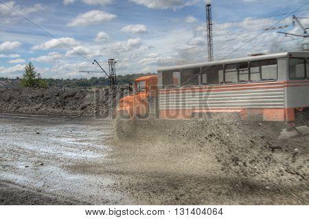 Poltava Region Ukraine - June 26 2010: Mining crew bussplashes driving at high speed along the opencast with mud splashes