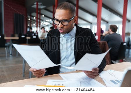 Angry businessman with documents and laptop at office