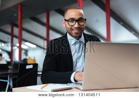 Young businessman typing on laptop in the office
