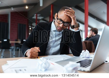 Focused businessman thinking over laptop