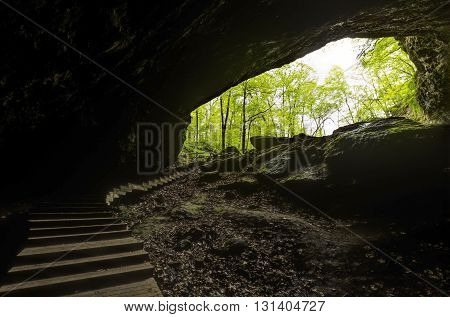 Inside a cave looking out with stairs leading out.