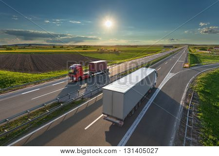 Two new modern trucks driving towards the sun at idyllic sunny day. Fast blurred motion drive on the freeway. Freight scene on the motorway near Belgrade Serbia.
