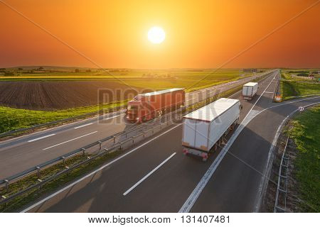 Three big trucks driving towards the sun. Fast blurred motion drive on the freeway at beautiful sunset. Freight scene on the motorway near Belgrade Serbia.