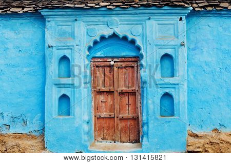 Blue painted traditional rural house with closed wooden door in Madhya Pradesh, India