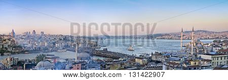 ISTANBUL TURKEY - APRIL 22 2016: Panoramic image of Istanbul with Galata Bridge and Yeni Cami Mosque during sunset.