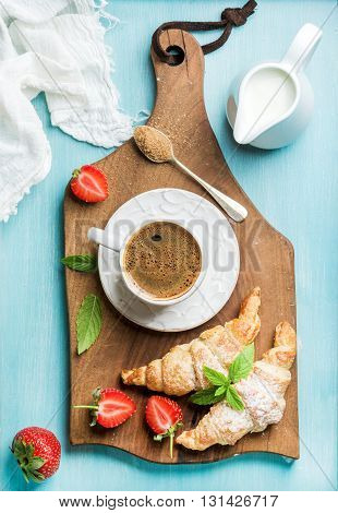 Breakfast or dessert set. Freshly baked croissants with strawberries, cup of coffee and milk in creamer on brown wooden board over blue background, top view