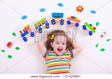 Child playing with wooden train. Toy railroad for kids. Toddler kid at day care. Educational toys for preschool and kindergarten child. Little girl at daycare.