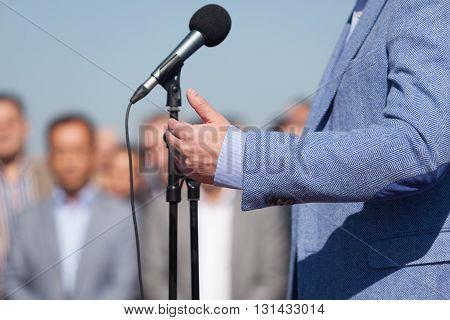 Speaker. Speech. Microphone. News Conference. Politician or businessman speech.
