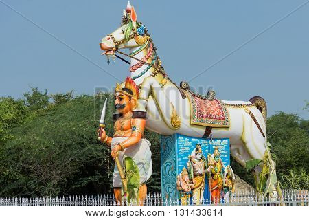Chettinad India - October 16 2013: Ayyanar and his horse at his shrine in Pilivalam village.Tableau of Lord Shiva family under the horse belly. Blue sky.
