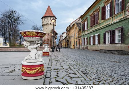 SIBIU, ROMANIA - MARCH 2016: Downtown pedestrian street with a child statue near castle in Sibiu with dark sky on 8th of March in Sibiu, Romania