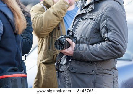 The Person Standing In Crowd Holds In Hand The Camera