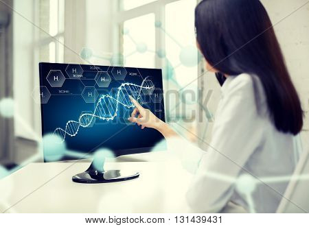 people, technology, biology, genetics and science concept - close up of woman pointing finger to dna molecule on computer monitor in office