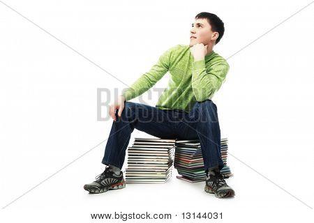 Retrato de un joven sentado sobre una pila de libros. Carrera de educación, éxito.