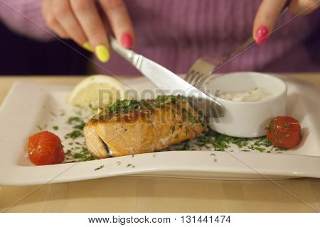 hands of the woman cutting a stake from fish on a plate in cafe