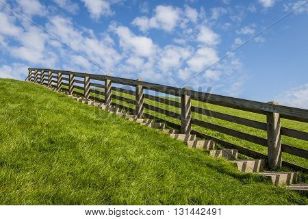 Stairs on a green grass dike in Friesland in the summer in the Netherlands.