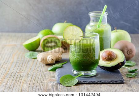Green fresh detox vegan smoothie healthy beverage vitamins diet drink with spinach avocado lime ginger kiwi apple. Morning organic drinking