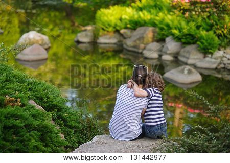 Woman and boy sitting on the bank of the pond. They sit huddled together other. Boy hugging a woman. A couple admiring the beautiful small pond. Quiet water reflects a coastal bush. Peace and harmony