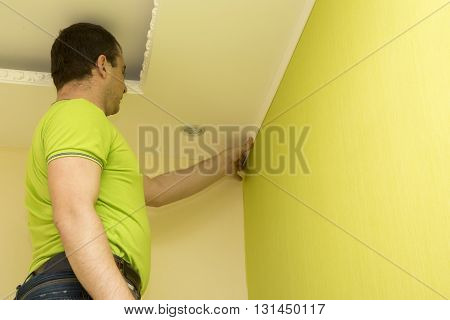 Constructor installing white plastic molding to decorate ceiling and wall