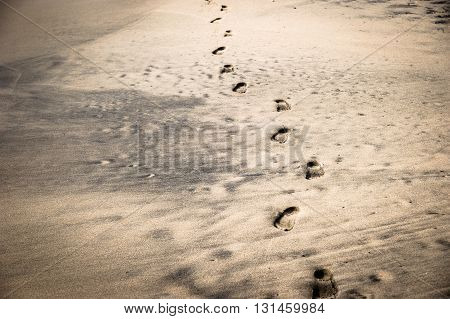 FOOTPRINTS ON BLACK AND YELLOW SAND BEACH
