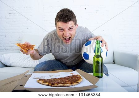young man watching football game on television celebrating goal crazy happy sitting on sofa couch at home holding and pizza with beer bottle looking excited and cheerfull