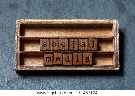 Social media retro style text. Vintage blocks with letters, aged wooden box frame. Gray stone background, macro