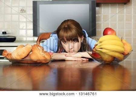 Young woman making a choice what to eat.
