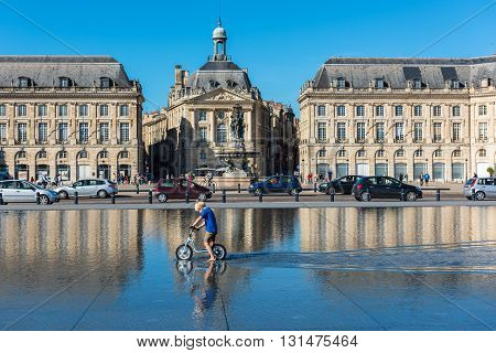 Children Having Fun In A Mirror Fountain In Bordeaux