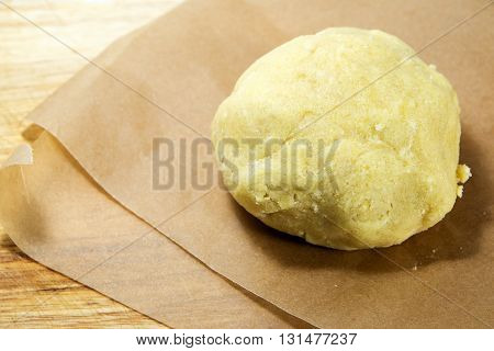 Fresh ball of raw shortcrust dough on baking paper ready to roll it out selected focus narrow depth of field