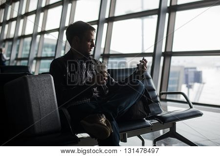man waiting at airport lounge texting with his smart phone.