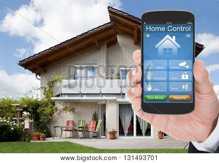 Close-up Of A Hand Holding Mobile Phone With Home Control System In Front Of House