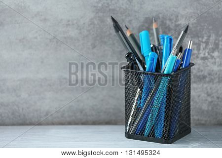 Pens and pencils in metal holder in front of wall background
