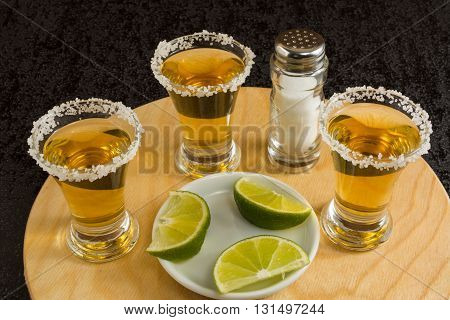 Gold tequila shots with lime and salt on the round wood board. Tequila. Gold Mexican tequila. Tequila shot. Alcohol drink