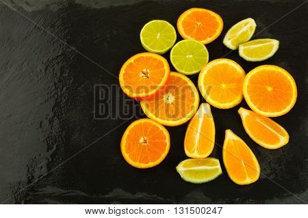 Limes oranges and lemons on black background copy space. Fresh food. Ripe fruit. Citrus fruit. Vegetarian food. Fresh fruit. Mixed fruit. Fruit background.
