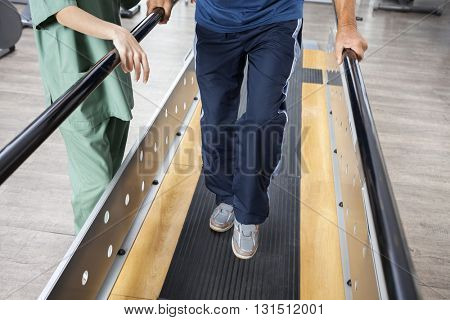 Senior Man Walking With Support Of Bars By Female Physiotherapis