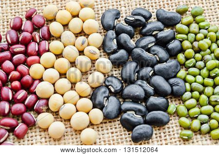 Red or azuki bean yellow or soy bean black bean and green or mung bean on sack background.