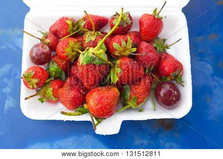 Strawberries in box on blue background for eat
