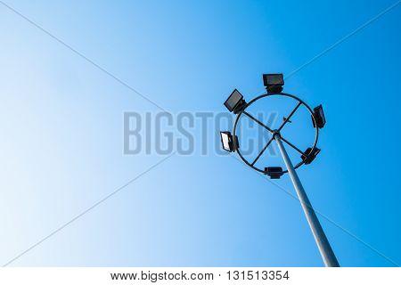 Big spotlight pole on blue sky background